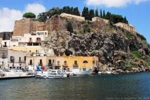 Marina Corta verso nord con la cinta muraria del Castello di Lipari realizzate su rocce vulcaniche a strapiombo sul mare