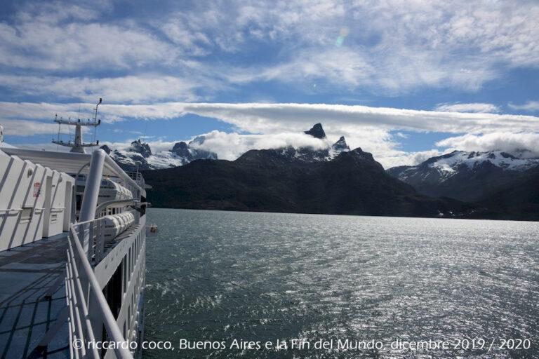 Avvicinamento al ghiacciaio Aguila nel Fiordo Agostini o Seno Agostini in Cile che divide in due la Cordigliera di Darwin. Sullo sfondo il Monte Buckland (a sinistra) con la cima coperta di nuvole. Al centro dell'immagine il Monte Sella.