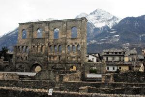 """Suggestiva immagine del teatro romano di Aosta con le """"grandi"""" montagne che sovrastano la città"""