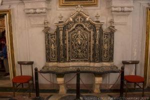 Lo scanno ligneo di mogano riservato ai Superiori della Compagnia, addossato alla controfacciata, in legno dorato intarsiato con avorio e madreperla.